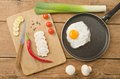 Fried egg in a frying pan on wooden background Royalty Free Stock Image