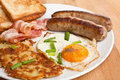 Fried egg hash browns and bacon breakfast plate with classic on a wooden table Stock Photography