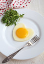 Fried egg in a heart shape with rocket anf fork in white plate o and on table Stock Photo
