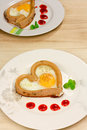 Fried egg heart shape to be served with salt and pepper Stock Photography