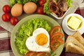 Fried egg on heart shaped toast with salad traditional breakfast bacon eggs and Royalty Free Stock Photo