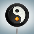 A fried egg philosophy an yin yan symbol made of in pan Stock Image
