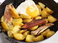 Fried egg potatoes and veal sausage frying pan filled with meatloaf bavarian Stock Photography