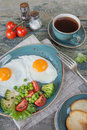 Fried eggs,  bacon, tomato, toast and a cup of coffee Royalty Free Stock Photo