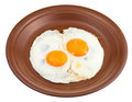 Fried eggs on ceramic brown plate two isolated white background Royalty Free Stock Image