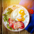 Fried eggs with fresh vegetables on the plate Stock Photo