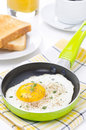 Fried eggs in a frying pan crisp toast coffee and orange juice for breakfast vertical Royalty Free Stock Images