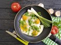 Fried eggs in frying pan,knife fork cook breakfast rustic , green onions, tomato, black wooden background