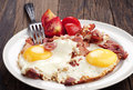 Fried eggs with ham and tomato on wooden table Royalty Free Stock Photography