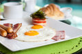 Fried eggs with sausage bacon ham and tomato cheese breakfast Stock Images