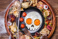 Fried eggs in the shape of a skull and fresh tomatoes. Breakfast in Halloween decorations.
