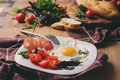 Fried eggs with tomato, basil and prosciutto, table set for cozy breakfast Royalty Free Stock Photo