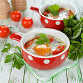 Fried eggs with vegetables on a white table Royalty Free Stock Images