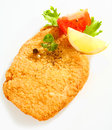 Fried escalope of veal with lemon close up view the crispy golden surface a pan in breadcrumbs tomato and parsley on a white Royalty Free Stock Photo