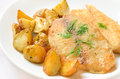 Fried fish fillet with baked potatoes on white plate Stock Image