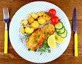 Fried fish fillet with rosemary potatoes and vegetables top view Stock Photography
