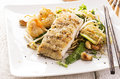Fried fish with noodles and vegetables fired as closeup on a white plate Royalty Free Stock Image