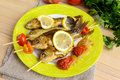 Fried fish (carp) on skewers with pieces bell pepper, sun-dried tomatoes and lemon Royalty Free Stock Photo