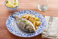 Fried gilt head bream with potatoes in a restaurant table Royalty Free Stock Photography