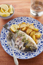 Fried gilt head bream with potatoes in a restaurant table Royalty Free Stock Photos