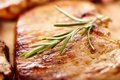 Fried pork chop decorated with rosemary closeup of spiced on a wooden board selective focus Stock Image