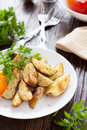 Fried potato wedges with herbs on white plate Royalty Free Stock Images