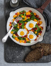 Fried quail eggs and vegetables - healthy breakfast or snack. On a wooden table Royalty Free Stock Photo