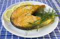 Fried salmon on a plate with lemon and dill on a blue checkered table cloth Stock Photos