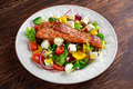 Fried Salmon steak with fresh vegetables salad, feta cheese. concept healthy food. Royalty Free Stock Photo