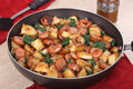 Fried sausage and potatoes with spinach in a skillet Stock Photo