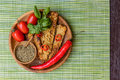 Fried tempeh, chili peppers, fresh cherry tomatoes, basil leaves, mix of herbs and sea salt in wooden pots with wooden spoons on a Royalty Free Stock Photo