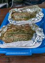 Fried trout in foil on a blue plastic tray