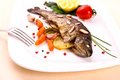 Fried trout with vegetables and split almonds on white plate close up Royalty Free Stock Images