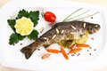 Fried trout with vegetables and split almonds on white plate top view Stock Photo