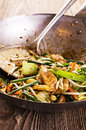 Fried vegetables and chicken in wok stir as closeup Stock Photos