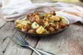 Fried young potatoes with chanterelles mushrooms in bowl on old Royalty Free Stock Photo