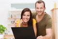 Friendly attractive young couple working on a laptop together in the kitchen or living room posing together arm in arm smiling for Stock Photo