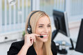 Friendly call centre operator or receptionist attractive young female wearing a headset and listening to the conversation with a Royalty Free Stock Photography
