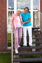 Friendly carer helping a senior lady on steps smiling female walk down flight of exterior wooden holding her by the hand for Royalty Free Stock Image