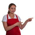 Friendly chinese waitress pointing to the right smiling in a red apron Royalty Free Stock Photo