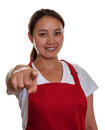 Friendly chinese waitress pointing to you in a red apron the camera Stock Photography