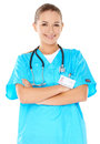 Friendly confident female doctor or nurse with a beautiful smile in green scrubs with a stethoscope around her neck isolated on Stock Photography