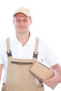 Friendly delivery man or workman with a package in dungarees brown cardboard under his arm wearing peak cap Stock Photo