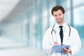 Friendly doctor with clipboard smiling standing in hospital hallway Royalty Free Stock Photo
