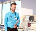 Friendly doctor in modern office standing at desk holding tablet smiling Royalty Free Stock Image