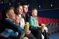 Friendly family with interest watching a movie and eating popcorn in the cinema Royalty Free Stock Photos
