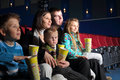 Friendly family watching a movie and eating popcorn in the cinema Royalty Free Stock Photos