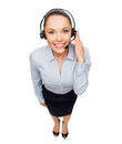 Friendly female helpline operator with headphones Royalty Free Stock Photo