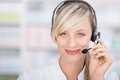 Friendly female pharmacist with headsets portrait of a looking at camera using and holding the microphone Royalty Free Stock Photo