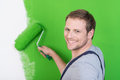 Friendly handsome handyman or painter turning to smile at the camera as he paints a wall in a house bright green Royalty Free Stock Photo